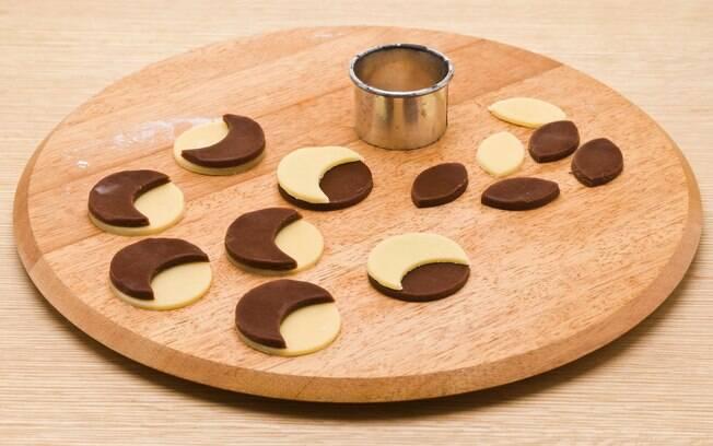 Abra a massa restante novamente e corte a mesma quantidade de círculos pretos e brancos. Faça meias-luas usando o cortador