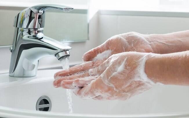 pessoa lavando as mãos em uma pia.