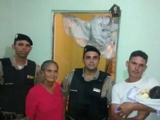 Soldado Gustavo Fiuza (à esquerda) e cabo Marconi Rocha entregam donativos ao pai e à avó do bebê