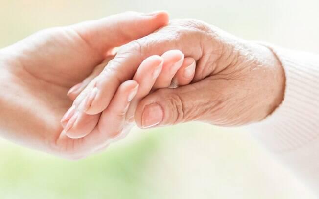 jovem segurando mão de idosa com unhas feitas