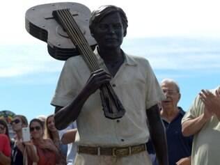 A estátua mostra Tom Jobim com um violão apoiado no ombro direito