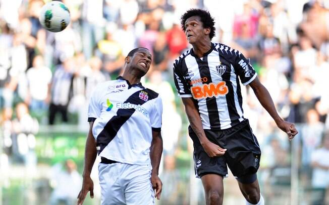 Dedé, do Vasco, briga pela bola com Jô, do  Atlético-MG