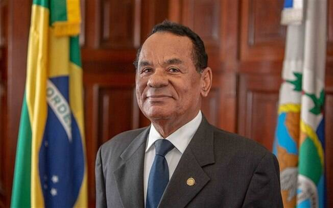 homem de terno e gravata diante de bandeira do brasil e do rio de janeiro