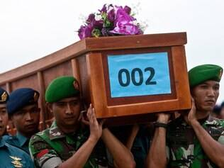 Militares indonésios carregam o caixão de uma vítima do voo da AirAsia QZ8501