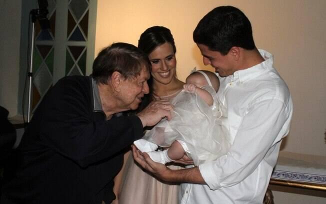 Boni paparica a neta Maria Luiza, no colo de Fernanda Pontes e Diogo Boni, após o batizado