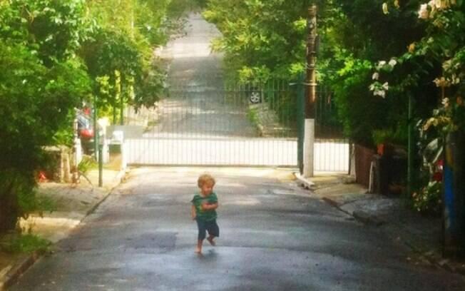 Criança brinca em rua sem saída cujo acesso é protegido por um portão, na Vila Mariana