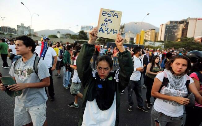 Jovem segura livro marcado em espanhol com a frase 'Esta é a minha arma' durante protesto contra repressão de estudantes em Caracas, Venezuela (13/2)