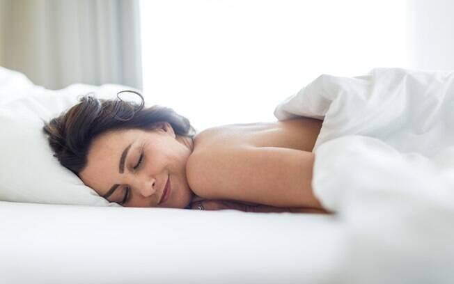 Mulher dormindo sem roupa coberta por um lençol