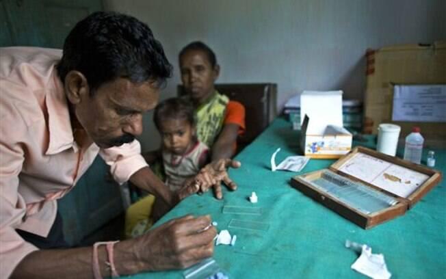 Na Índia, assistente coleta amostra de sangue de idosa com suspeita de ter adquirido malária