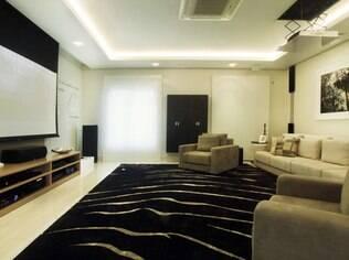Escolha um tapete confortável para o home theater, mas deixe uma área sem cobertura para a passagem. Projeto de Cristiane Schiavoni