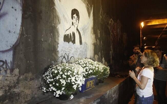 Cissa Guimarães reza em frente a figura em estêncil com o rosto do filho