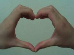 A mão de Bernardo, soropositivo, fazendo coração com a mão do namorado. Ambos têm menos de 25 anos e descobriram juntos serem portadores do vírus HIV