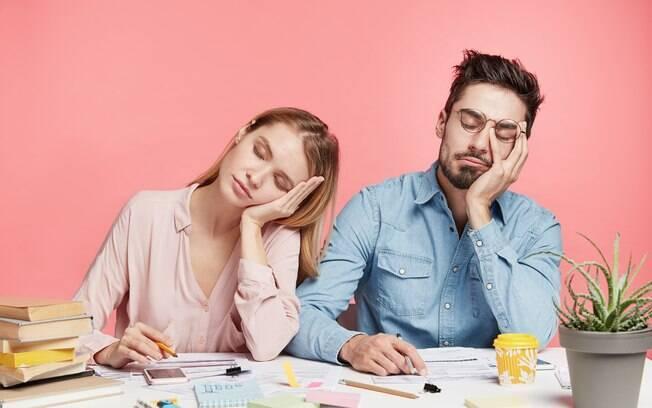 Homem e mulher cansados dormindo com a cabeça apoiada na mão