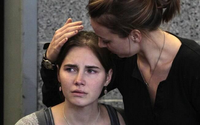 Amanda Knox (E) é consolada pela irmã, Deanna Knox, durante coletiva após sua chegada ao Aeroporto Internacional de Seattle, nos EUA