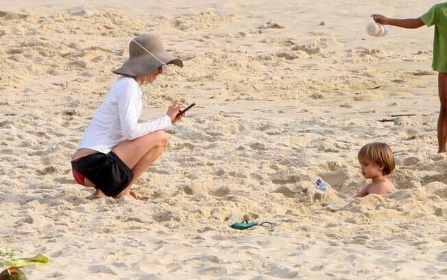 Fernanda Torres fotografa Antonio dentro de um buraco na areia