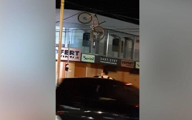 Bicicleta foi parar na rede elétrica após caminhão passar sobre os fios.