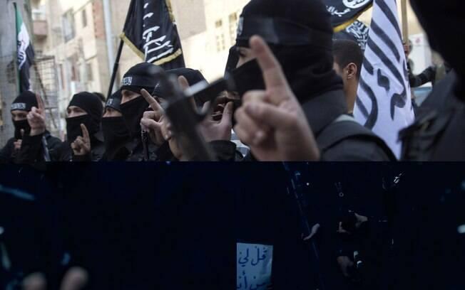 Membros de grupo islâmico seguram armas durante protesto contra regime em Deir el-Zor (25/02)