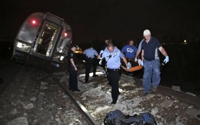 As equipes de emergência trabalham no local onde o trem descarrilou, na noite de terça-feira