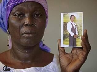 Martha Mark, mãe de Monica Mark%, uma das sequestradas em escola nigeriana chora ao mostrar foto da jovem na casa da família