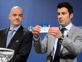 Former Portuguese  soccer player Luis Figo, right, shows a ticket with Spain's soccer team Real Madrid CF next to UEFA General Secretary Gianni Infantino, left, during the draw of the quarterfinals of UEFA Champions League 2013/14 at the UEFA Headquarters in Nyon, Switzerland, Friday, March 21, 2014. (AP Photo/Keystone,Laurent Gillieron)