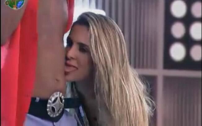 Joana lambe a barriga de Dinei durante a festa black