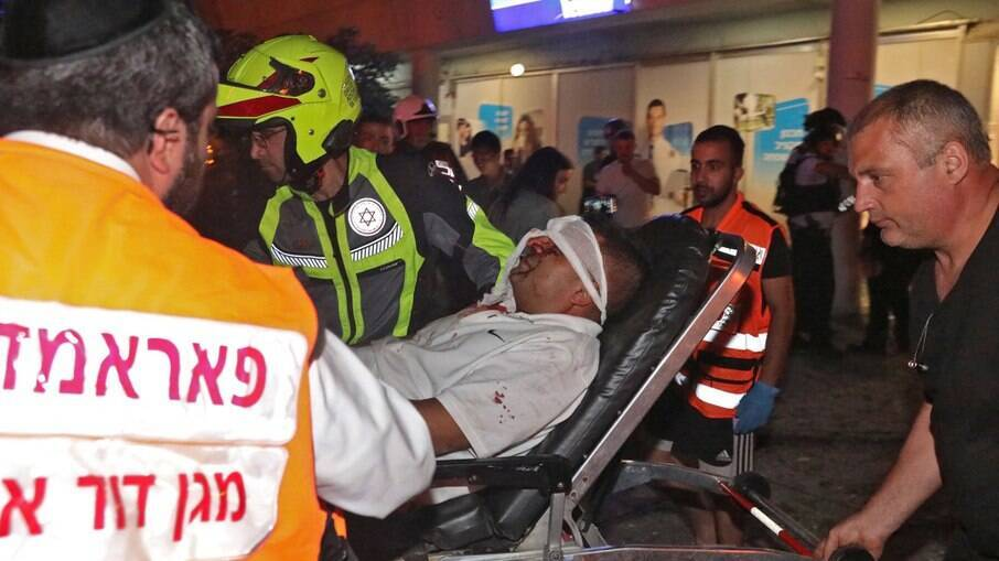 Serviços de emergência israelenses transportam um homem ferido na cidade de Holon, perto de Tel Aviv