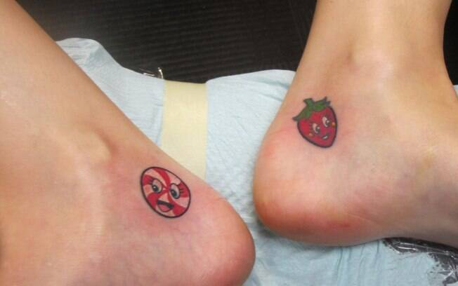 No tornozelo esquerdo, o morango feito aos 25 anos de idade. No tornozelo direito, a última tatuagem, uma bala sorridente
