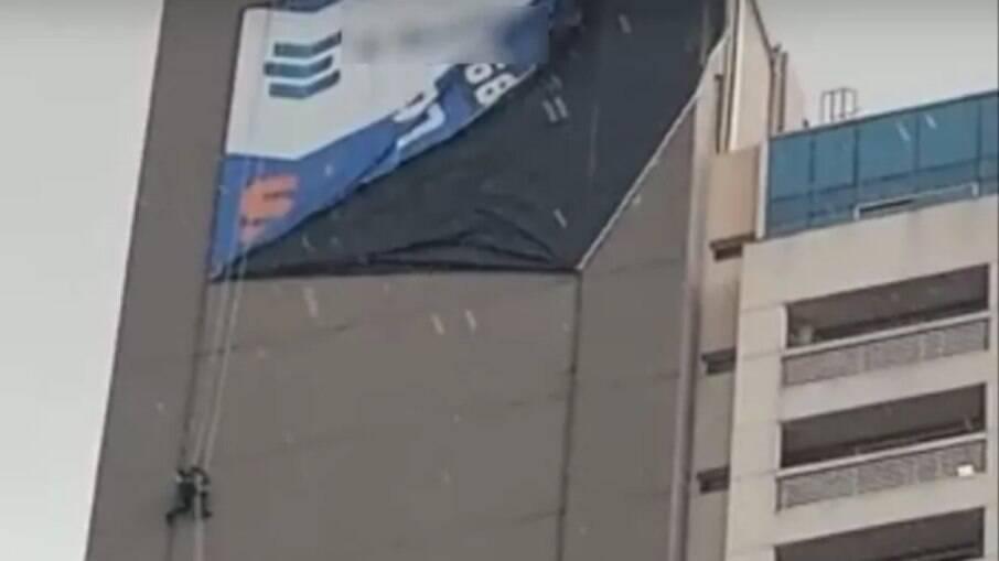 Homem fica pendurado em fachada de prédio ao instalar lona em meio ao temporal.
