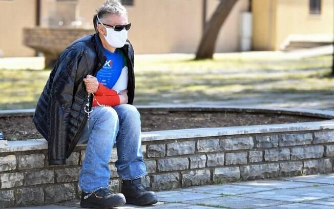 Home de máscara facial sentado em banco de pedra