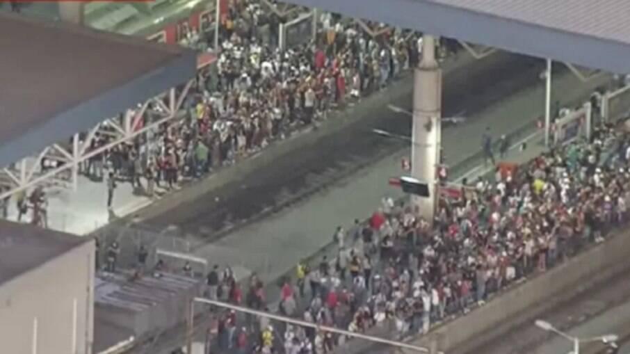 Pessoas aglomeradas na plataforma esperando o trem