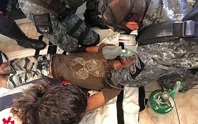 PMs do GATE e médicos do SAMU prestam os primeiros socorros. Note os dedos e camiseta ensanguentados do indivíduo que se auto mutilou com uma faca