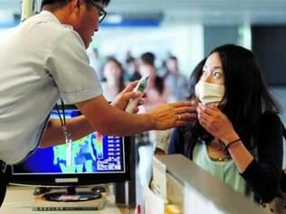 Segurança. Agente em aeroporto na Coreia do Sul reforça medidas de controle da disseminação do vírus