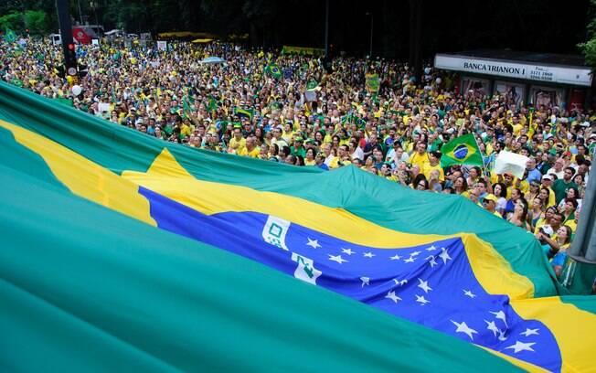 Manifestantes erguem bandeira do Brasil durante o maior ato da história do País, em São Paulo