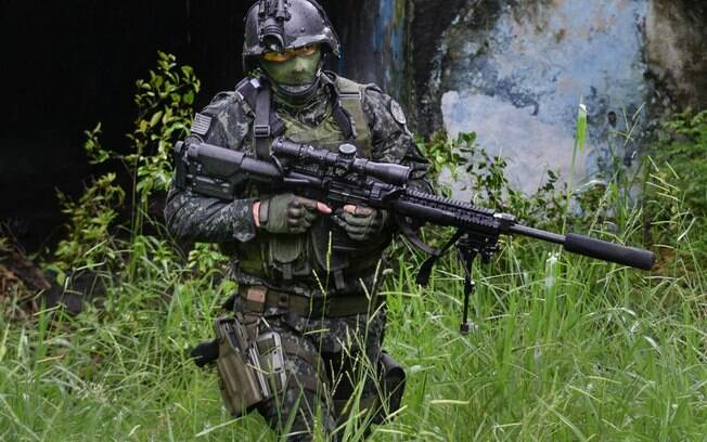 Atirador de Precisão (Sniper) do COE procurando local de tiro. Repare nos acessórios especializados do seu rifle: luneta, bipé frontal para estabilidade e supressor de som na ponta do cano. No capacete, equipamento de visão noturna