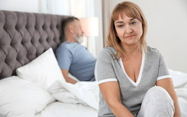 mulher sentada na cama, triste, homem ao fundo sentado na cama