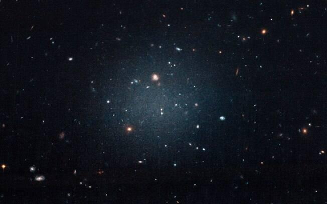 NGC1052-DF2 é tão difusa que podemos ver através dela. O movimento das estrelas nesta galáxia indica a ausência de matéria escura.