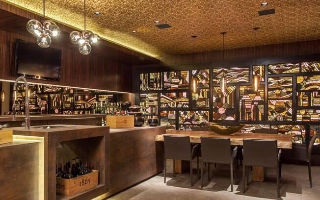 No teto do bar planejado por Maithiá Guedes, o papel de parede imita rolhas com um suave toque de brilho dourado