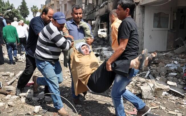 Homens carregam ferido após explosão em cidade turca perto da fronteira síria (11/05)