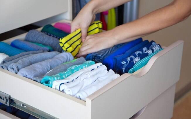 Para organizar o guarda-roupa, a recomendação é guardar as camisetas uma atrás da outra, conforme mostra a imagem