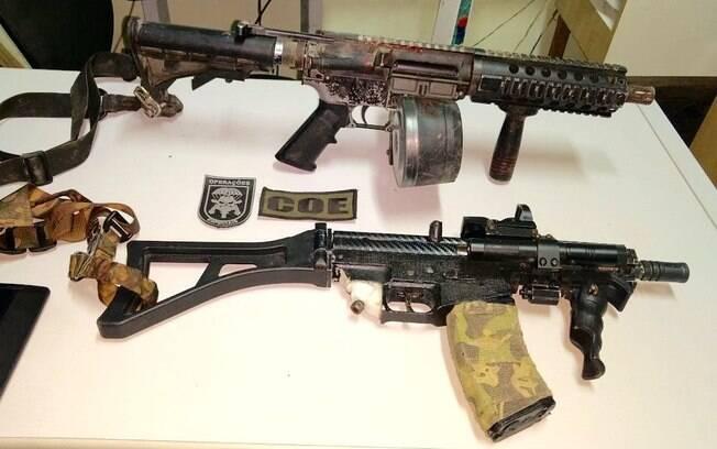 Em cima o fuzil Colt M4 5.56 com dois carregadores circulares com capacidade de 100 tiros. Abaixo a submetralhadora 9mm com mira laser (tubo redondo do lado direito do cano) e um designador holográfico (estrututa retangular acima do cano)