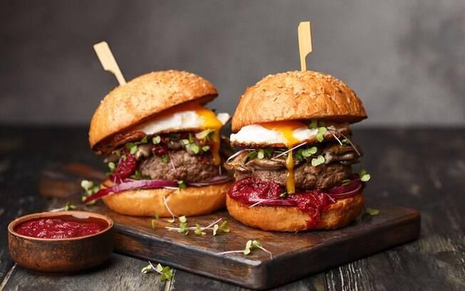 Dois lanches de hambúrgueres, um ao lado do outro, com um molho a parte para acompanhar a refeição.