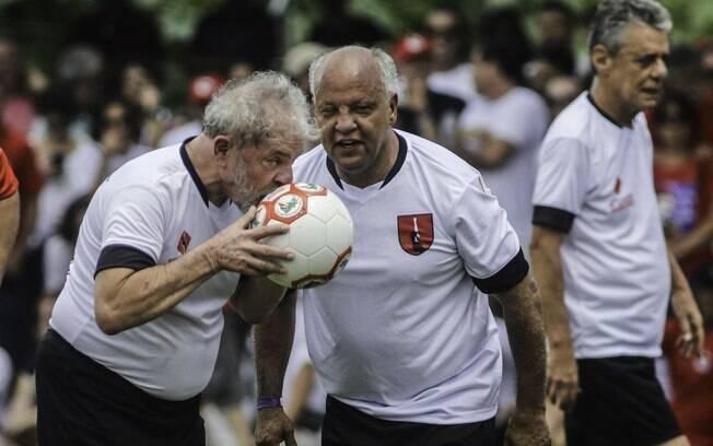 Lula antes de cobrança de pênalti durante inauguração de campo do MST; ao fundo, o cantor e compositor Chico Buarque