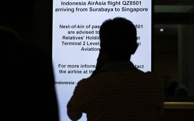 Familiar observa toten da AirAsia que informa sobre voo desaparecido. Foto: AP Photo/Wong Maye-E