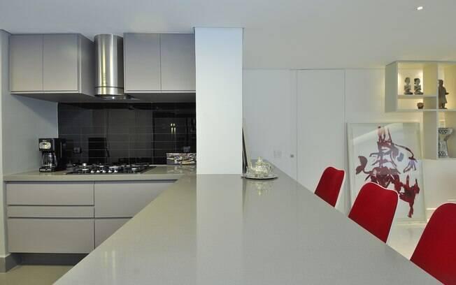 O cinza predomina na bancada e marcenaria desta cozinha. As cadeiras vermelhas dão o toque de cor e personalidade ao lado dos tons de cinza do ambiente