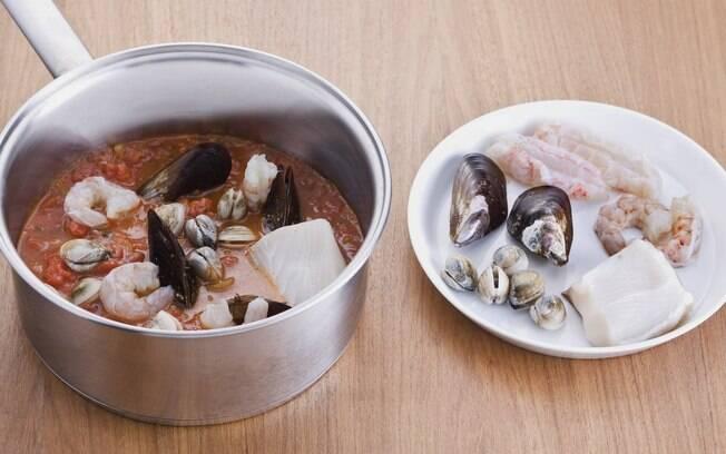 Arrumar a posta de cação e os frutos do mar sobre o caldo de tomate e ervas, temperar com sal e pimenta e adicionar o vinho