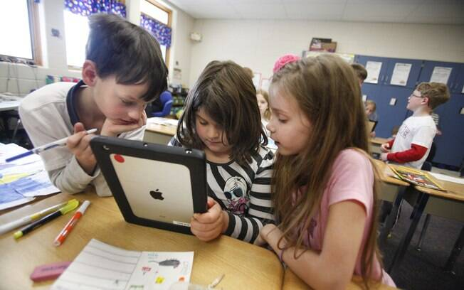 Colegas de classe de Julianna usam um iPad em sala