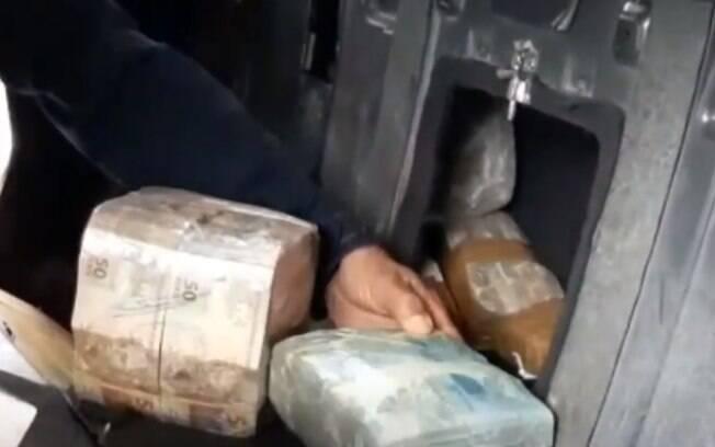 Polícia Rodoviária Federal encontrou o dinheiro em um fundo falso no banco de trás do carro.