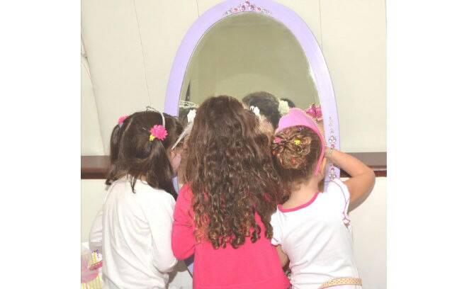 Na festa com desfile, as meninas também se divertem fazendo a própria maquiagem