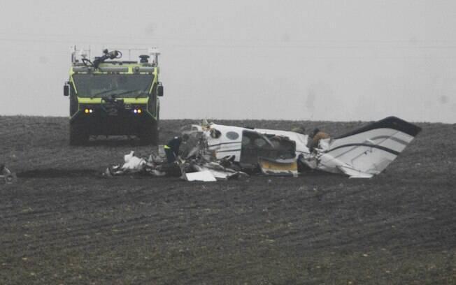 Os investigadores trabalham no local de um pequeno acidente de avião perto de Bloomington, EUA (7/04)