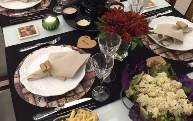 Mesa para fondue decorada com jogos americanos temáticos, velas e flores